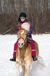 Young girl riding her pony bareback