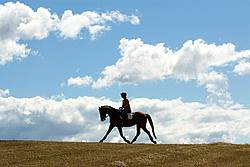 Woman horseback riding against big sky background