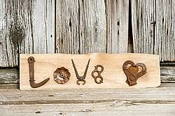 Hand crafted Love art sign made out of wood and recycled or repurposed farm tools and machinery parts