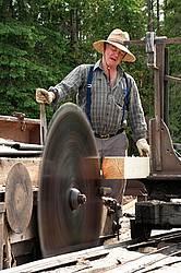 Man operating a circular saw mill on the farm