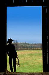Cowgirl silhouetted in barn doorway