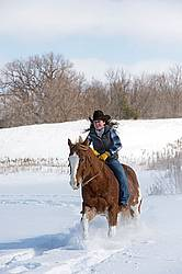 Young woman riding a horse bareback through deep snow