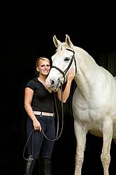 Young woman and white horse posing in barn doorway with black background