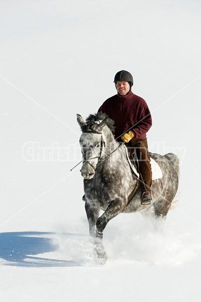 Man riding grey horse galloping through deep snow