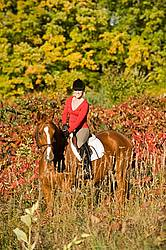 Young woman horseback riding in the fall of the year.