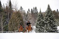 Man and woman horseback riding in the snow