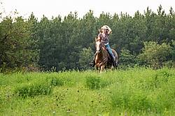 Young woman horseback riding western