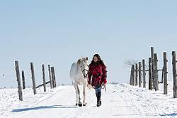Young girl leading horse