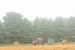 Farmer baling round bales of straw