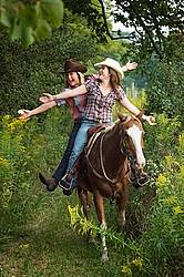 Two young women riding double in a western saddle