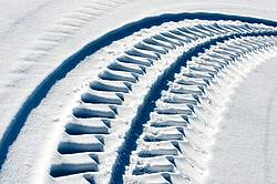 Photo of tractor tire tracks in the snow