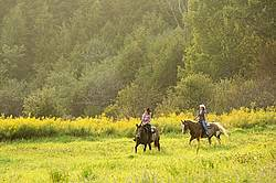 Two young women horseback riding western on a summer evening