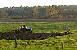 Farmer plowing field in the spring of the year with tractor and a three furrow plow