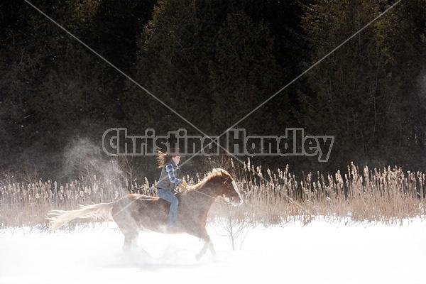 Young woman riding a horse bareback through deep snow