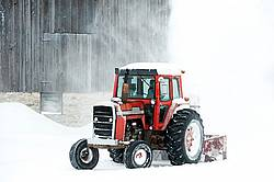 Snow blowing around the farm with a tractor and snow blower