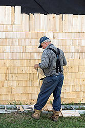Man putting cedar shingles on the wall of a barn