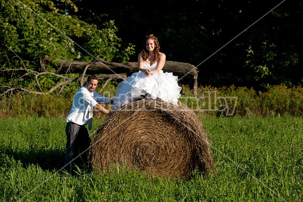 Bride and groom on round bale of hay