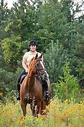 Young woman riding chestnut Thoroughbred horse.