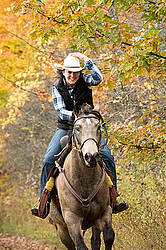 Young woman riding a Quarter Horse on trail