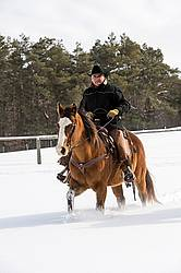 Portrait of a man horseback riding in the snow