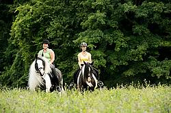 Two women riding Gypsy Vanner horses