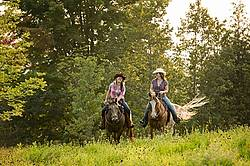 Two young women horseback riding western through summer pasture fields.