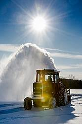 Farmer blowing snow