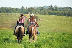 Two young woman horseback riding western goofing around stealing each others cowboy hats.