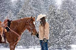 Young womand with horse in the snow