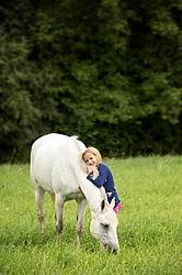 Portrait of a young girl hugging a gray pony in a field