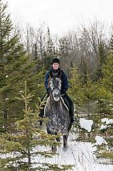 Woman riding Hanoverian mare through forest