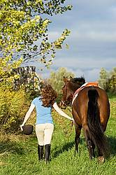 Young woman walking her horse on a grass path