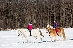 Two young girls riding their ponies in the snow