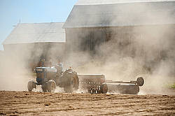 Farmer driving tractor and seed drill seeding oats