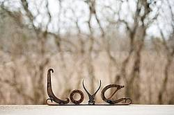 Hand crafted Love art sign made out of recycled or repurposed farm tools and machinery parts