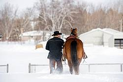 Portrait of a man walking a horse in the deep snow