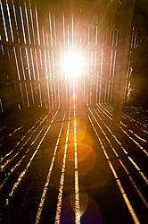Rays of sunshine beaming through barn boards